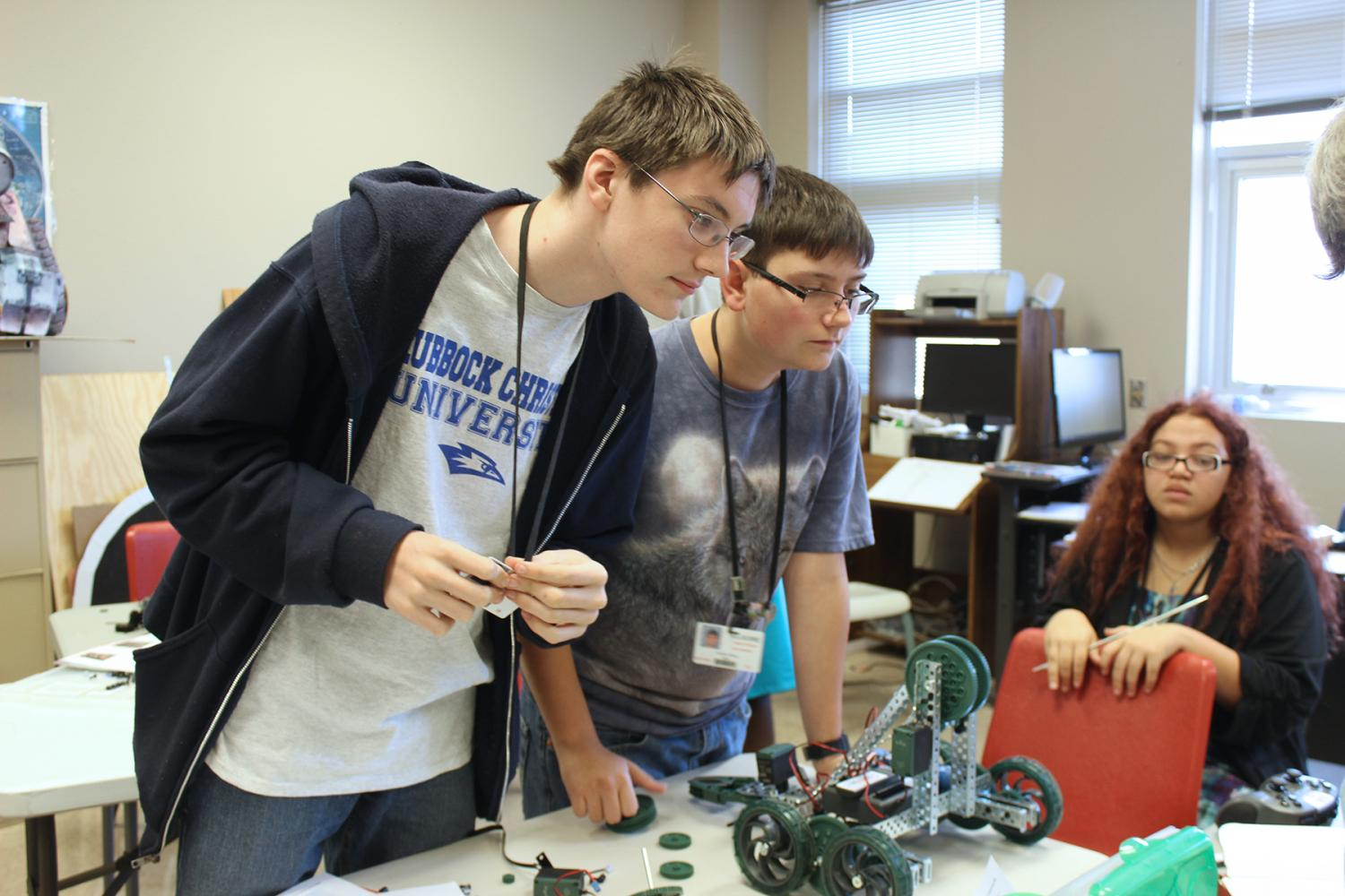 Sophomores Kendall Sloan, Justiss Ross, and Shelby Woods look over their robot.