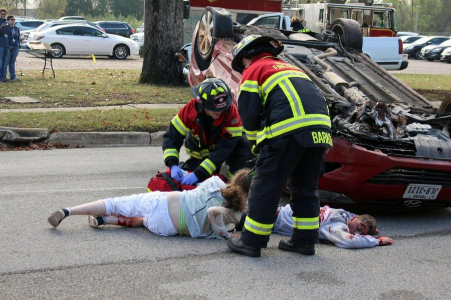 First responders approach mock victims and seniors Bailey Green and Elijah Williams.