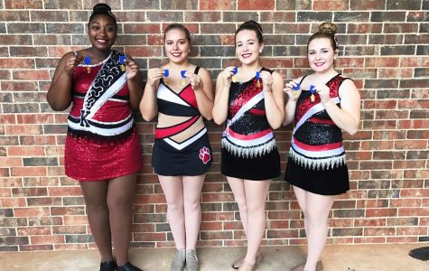 Twirlers hold their medals they received for making ones on their routines.  Twirlers are juniors Diamond Smith, Jordan Ware, sophomore Olivia Arp, and junior Hannah Howell.
