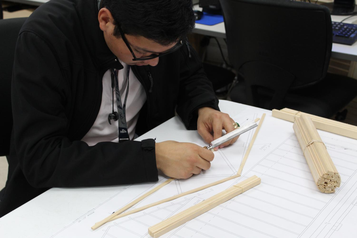 Junior Miguel Munoz takes the provided floor plan and wood to construct trusses for his group's model house.