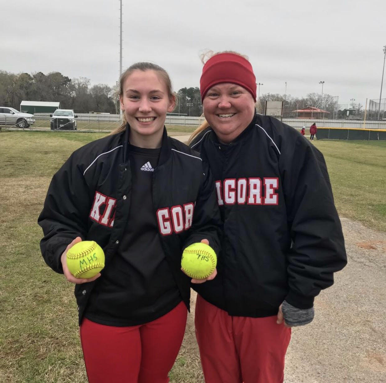 Coach Kirkpatrick and sophomore Bailey Hedges pose with her home run softballs.  Courtesy photo.