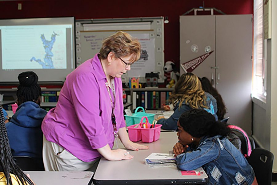 Miriam Cooper helps a student work on a project.