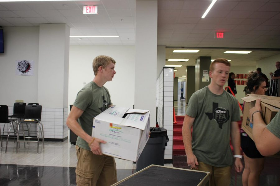 Junior+Kace+Murphy+and+senior+Josh+Young+unload+boxes+of+fixings+for+the+teachers.
