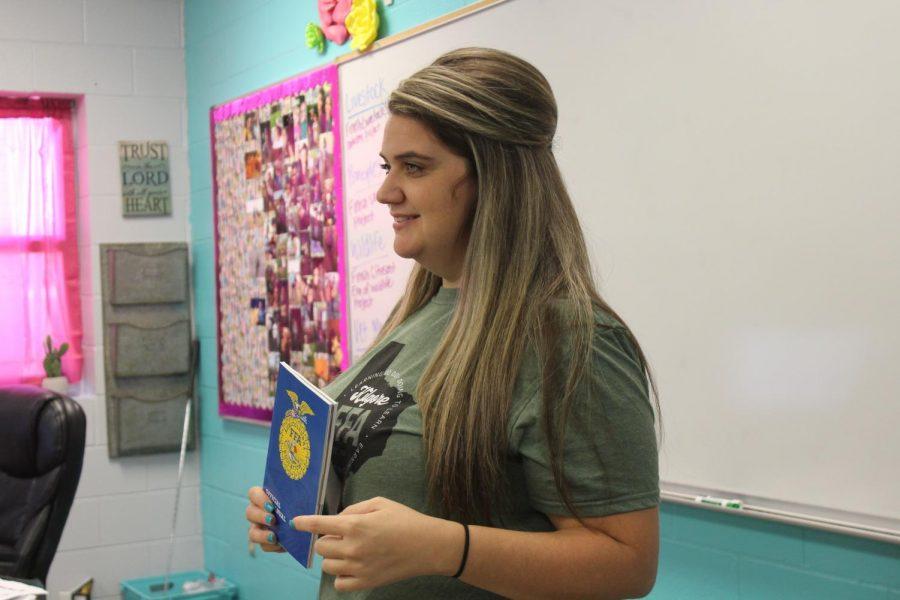 Macie Wagstaff shows students FFA booklet.
