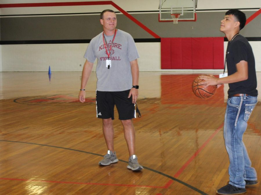PE and varsity football coach Blake Reeve plays basketball with PE student.