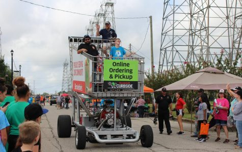 Brookshire's drives ambassadors Mason Riley and Sergio Najera down to the stage in the giant grocery cart.