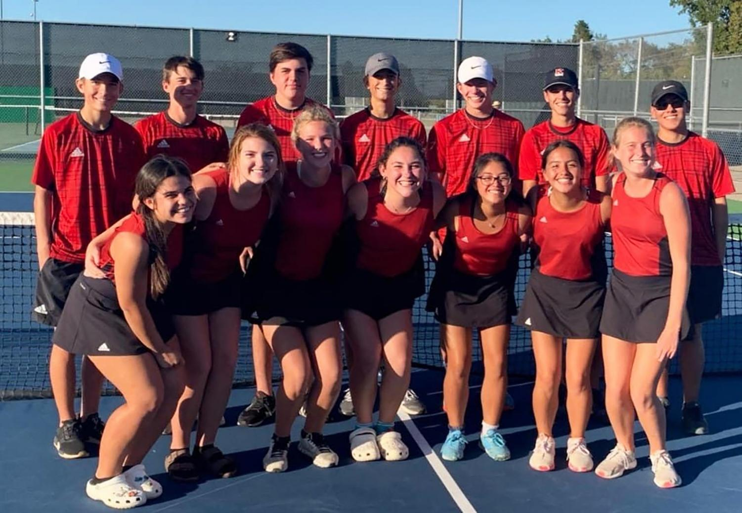 The tennis team celebrates their defeat against Crandall.
