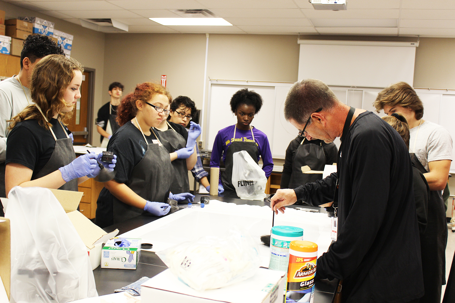 Coach Dean's forensic science class watches and learns how to properly dust for fingerprints.