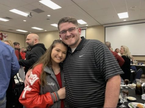 Junior Courtlyn Brown and senior Scott Silvey pose as boyfriend and girlfriend at football banquet.