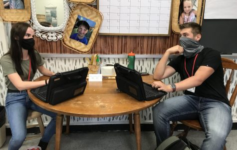 Juniors Karlee Menges and Jared Rich demonstrate the newest additions to the year. These additions are the school provided chromebooks and wearing a mask.