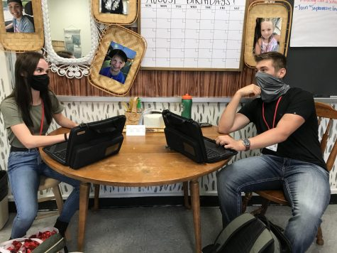 "Juniors Karlee Menges and Jared Rich demonstrate the newest additions to the year. These additions are the school provided chromebooks and wearing a mask. ""It"