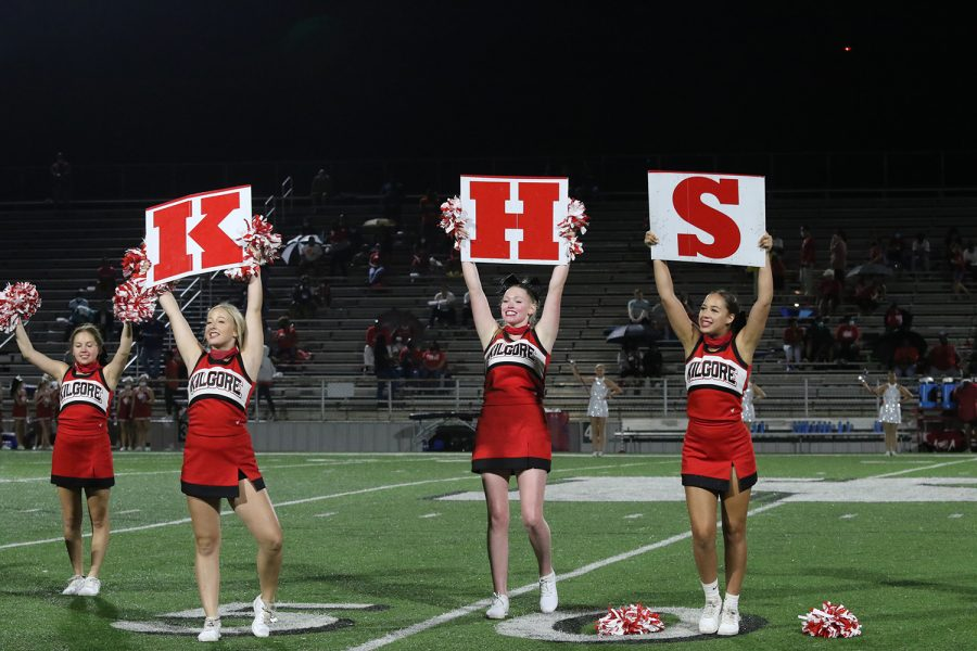 Sophomore Riley Thompson and Carley McEntire and Junior Jaiden Thompson hold up the KHS signs during halftime cheerr.