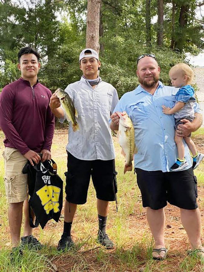 Seniors Efrain Mojica and Daniel Estrella stand with their sponsor Chris Smith and his son after a long day of fishing.
