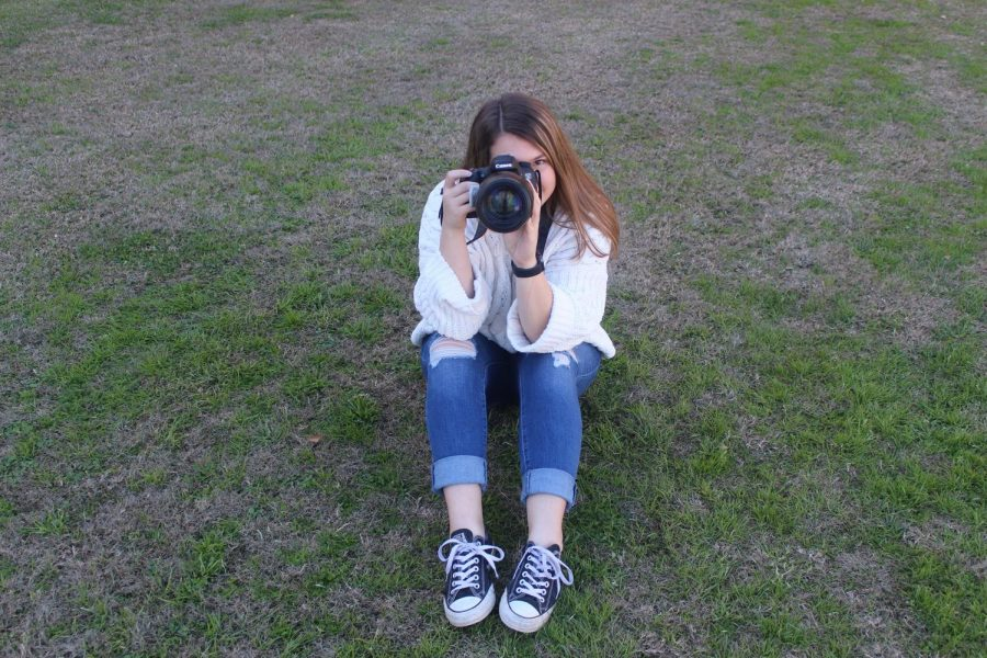 Senior Courtlyn Brown sits on lawn with camera.