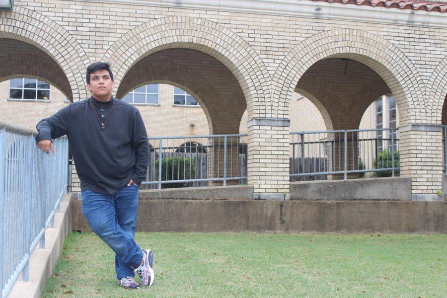 Senior Juan Vega poses   in courtyard.