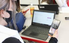 A student scrolls through social media while completing her Google Classroom assignment.